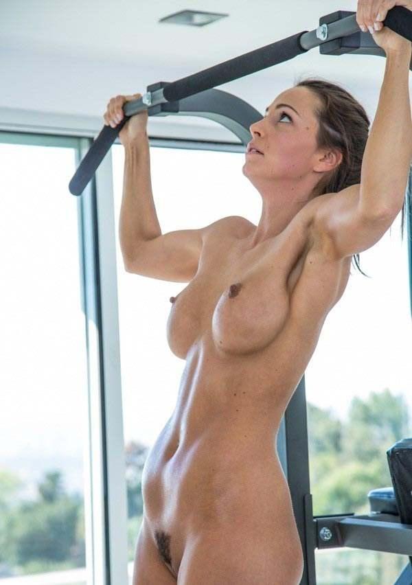 Голая мускулистая девушка подтягивается на турнике